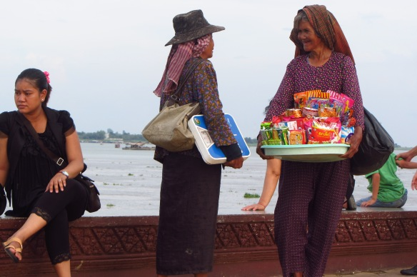 Old friends pause for a chat along the riverfront in Phnon Penh before continuing on with their sales.