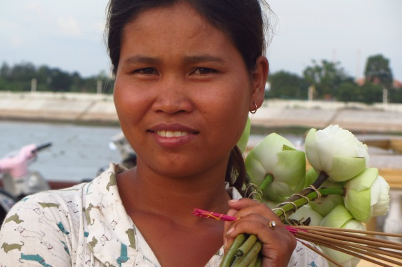 A beautiful young woman selling flowers outside a temple at the riverside in Phnom Penh.