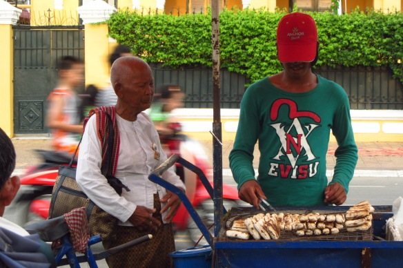 An old monk buys fried bananas from a young vendor on the street in Phnom Penh.