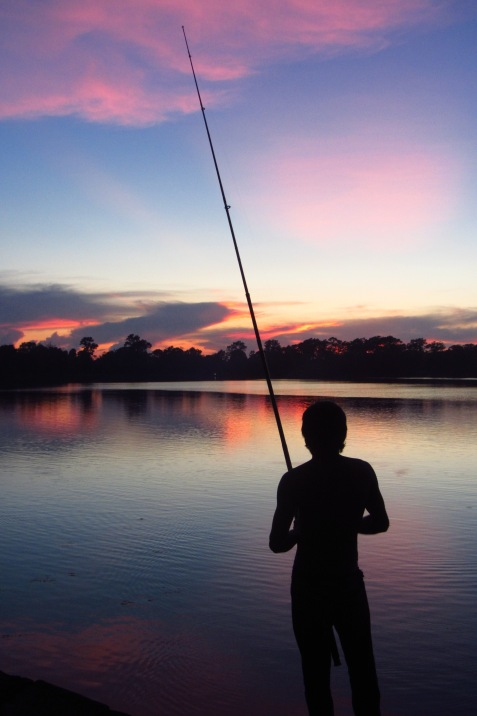 A fisherman silhouetted during sunset at Sras Srong lake in Siem Reap.