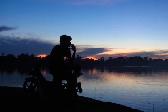 A moto driver pauses for a cigarette break to watch the sunset at Sras Srong lake in Siem Reap.