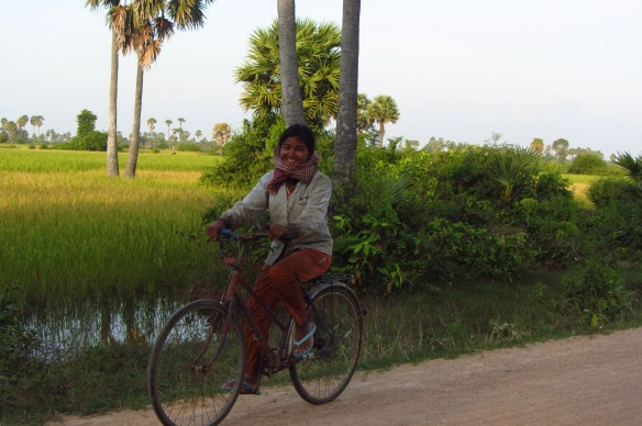A young woman biking home to her village after a long day working in the rice paddies.