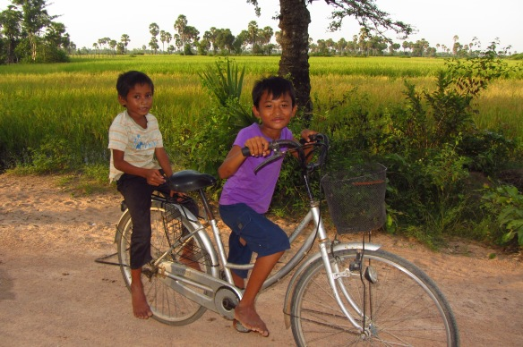 Samnang, 12,  (in purple), and Sokhorn out on a bike ride in Talak Village, Kampong Speu.