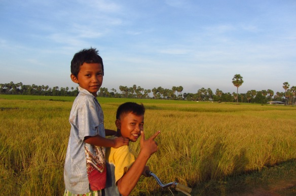 Mengleang, 8, and Bophan, 14, on a bike ride in Talak Village, Kampong Speu Province.