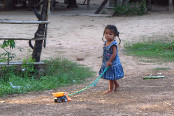 A village girl pulling her toy truck in Talak Village, near APCA.