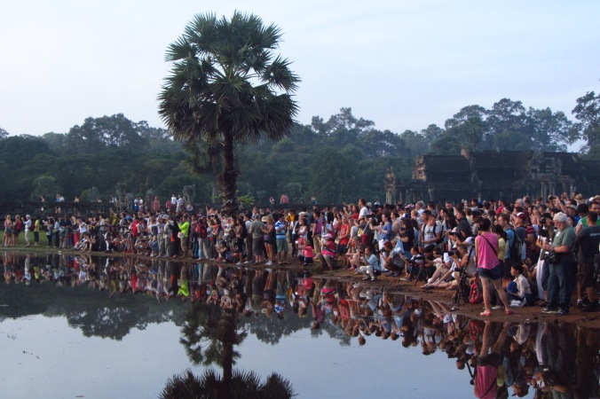 Hundreds of people gather at Angkor Wat to watch the magnificent sunrise.